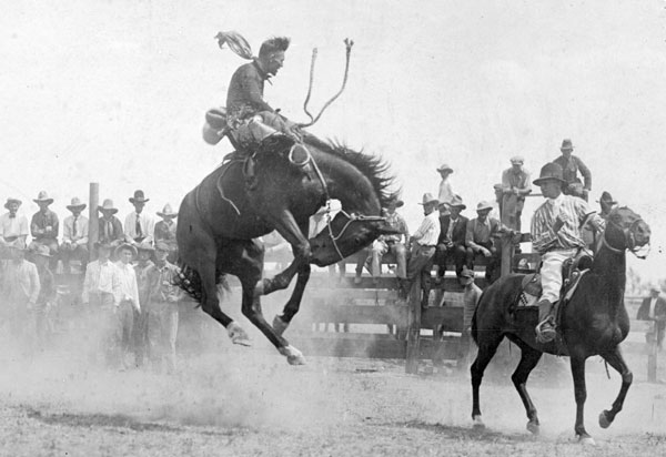 cowboy riding bucking horse in rodeo